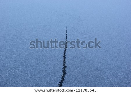 Crack in the ice on a frozen lake - risk concept - stock photo
