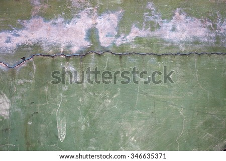 Crack line on the surface of a dilapidated green concrete wall. - stock photo