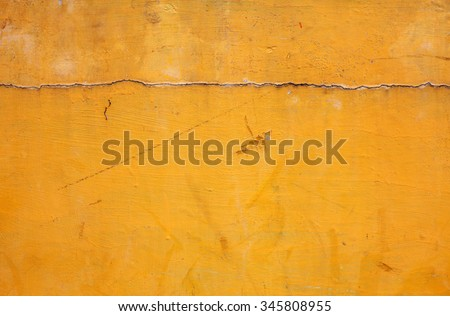 Crack line on the surface of a grungy yellow concrete wall.  - stock photo