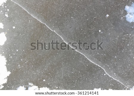 Crack on an ice surface of the frozen river, a natural background - stock photo
