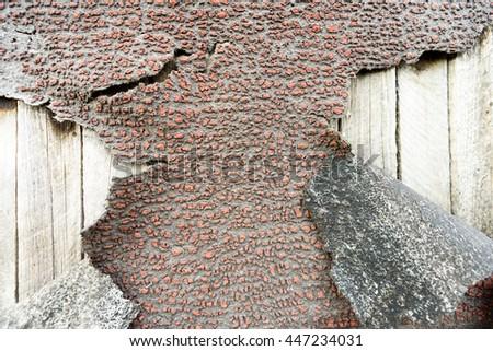 Cracked and peeling aged bitumen waterproofing coat on wood - stock photo