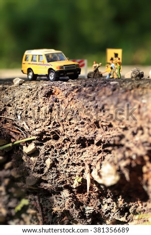 Cracked asphalt road and Roadworks with miniature figurines in a country setting.Soft Focus and Shallow Depth of Field Composition. - stock photo