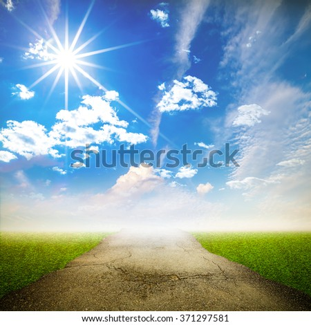 Cracked asphalt road with sunbeam and blue sky  in rural landscape. - stock photo