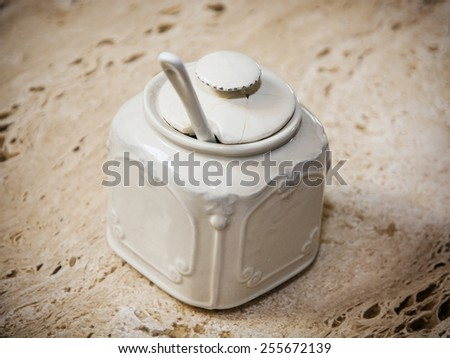Cracked ceramic sugar bowl on the retro table. - stock photo