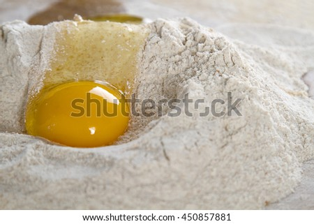 cracked chicken egg flowing in a nest of flour