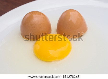 Cracked chicken egg with yolk and egg shell on dish background. - stock photo