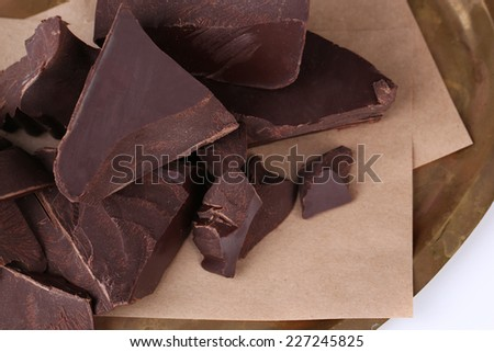 Cracked chocolate block on paper napkin isolated on white