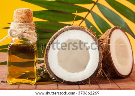 Cracked coconut and a bottle of oil on the table - spa, skincare, haircare and relaxation concept - stock photo