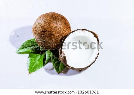 cracked coconut with big splash, isolated on white - stock photo