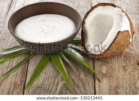 cracked coconut with milk cream in a clay bowl on wooden table surface - stock photo