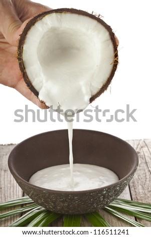 cracked coconut with milk splash  isolated on white background - stock photo