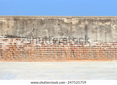 Cracked concrete vintage brick wall and blue sky background - stock photo