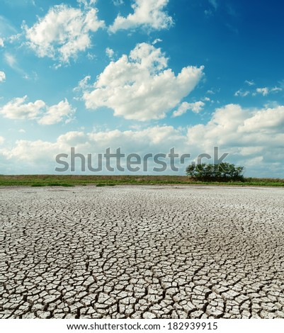 cracked desert under low clouds - stock photo