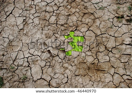Cracked dry earth as a puzzle (with green grass as one piece)