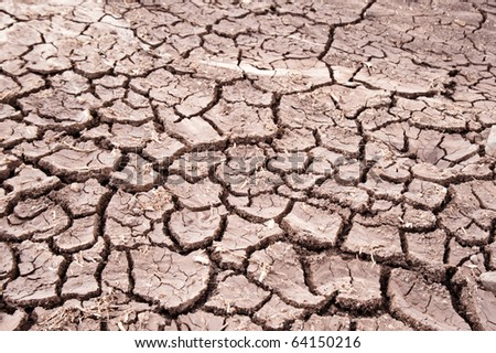 Cracked earth indicates dry weather, drought, or lack of water. - stock photo