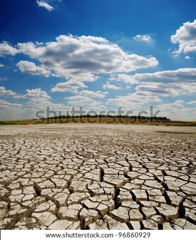 cracked earth under dramatic sky - stock photo