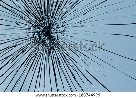 Cracked glass against a blue sky background - stock photo