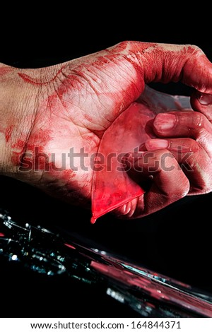cracked glass with blood in killer hand - stock photo