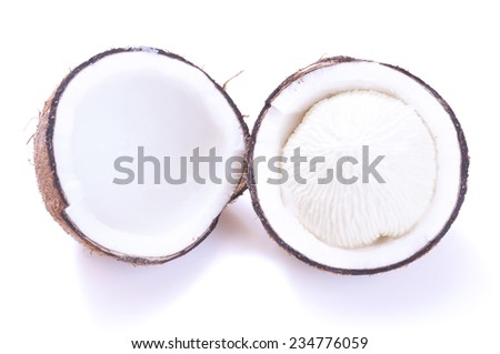 Cracked in half dehusked sprouted coconut with white spongy meat on white background - stock photo