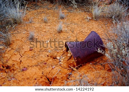 Cracked mud in the Australian outback near Woomera, featuring a rusted billy-tin. - stock photo