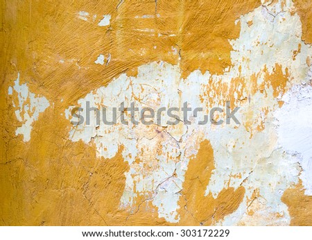 Cracked painted yellow concrete wall background or texture - stock photo