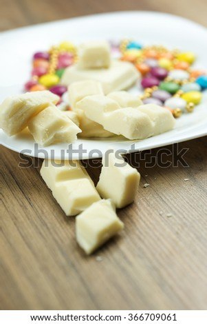 Cracked pieces of white chocolate on wooden table - stock photo