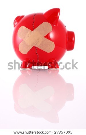 Cracked piggy bank with plaster representing financial problems - stock photo