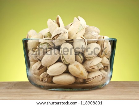 Cracked pistachio nuts in glass bowl on green background. - stock photo