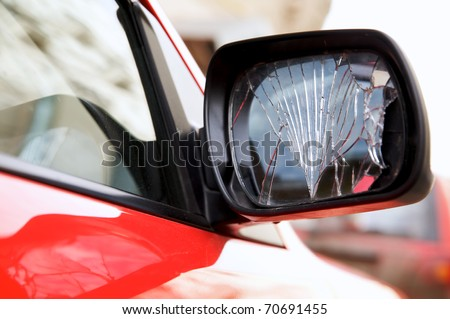 Cracked rear view mirror on a red car - stock photo