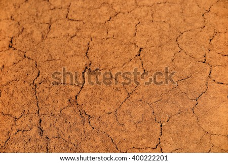 Cracked red clay soil - stock photo