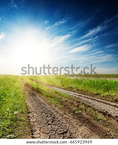 cracked road in green grass at sunset in a dark blue sky