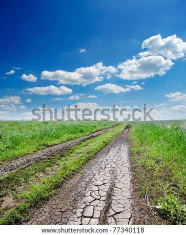 cracked rural road in green grass and cloudy sky - stock photo