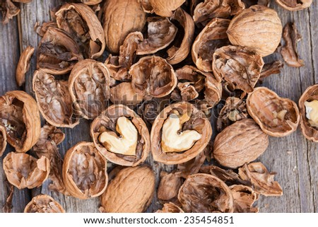Cracked walnuts on wooden background, close up. Heart shape. Also available in square format.  - stock photo