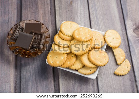 cracker and slices of chocolate in a vase on a wooden table - stock photo
