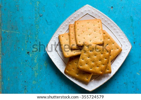 Cracker biscuits in a white ceramic square saucer on old blue background close-up. Free space for text. Copy space. Top view - stock photo