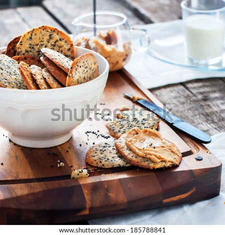 Cracker Cookies with Black Sesame Seeds and Peanut Butter as breakfast on the chopping board - stock photo