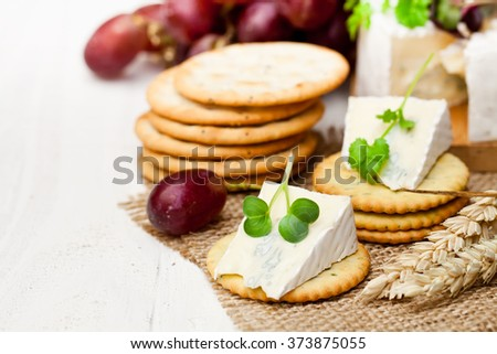 Crackers  and wedge of blue camembert cheese on sackcloth napkin