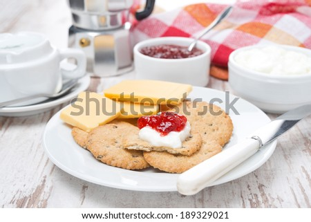 crackers with cheese, cream and jam for breakfast, horizontal