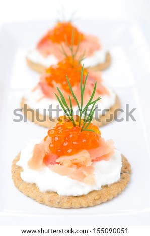 crackers with cream cheese, salted salmon and red caviar close-up selective focus vertical - stock photo