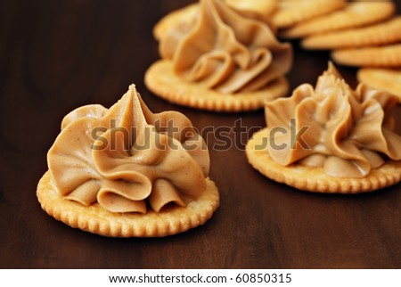 Crackers with creamy swirls of peanut butter on dark wood serving tray.  Macro with shallow dof. - stock photo