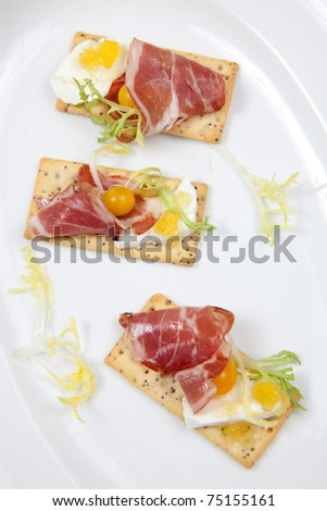Crackers with goat cheese, apricot spread, and yellow pear tomatoes wrapped to prosciutto - stock photo