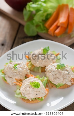 Crackers with tuna salad on white plate. - stock photo