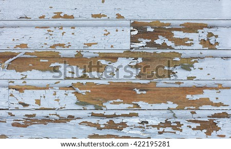 Cracking and peeling lead paint off of wood sliding.  - stock photo