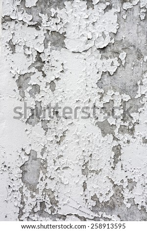 Cracking and peeling paint on a white concrete wall - stock photo