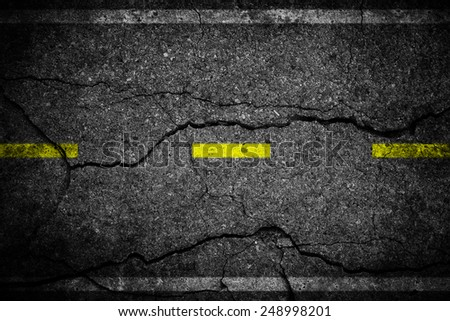 Cracks on asphalt the yellow line dividing lanes - stock photo