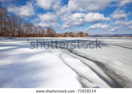 Cracks on the ice and the blue sky with clouds - stock photo