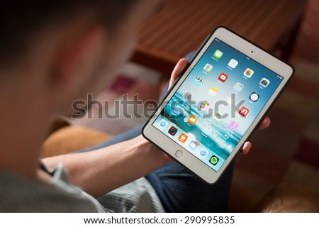 CRACOW - JUNE 26: Man uses the iPad mini 3 retina at his house in living room, Poland on june 26, 2015. - stock photo