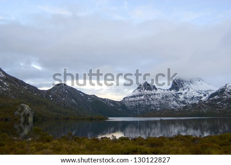 Cradle Mountain in Tasmania covered in winter snow reflected in the still water of the lake below