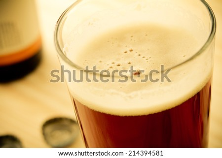 Craft Beer - This is a shot of a cold glass of beer shot at a high angle in a warm, retro color tone. Shot with a shallow depth of field. - stock photo