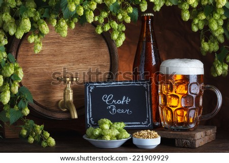 Craft bottled and unbottled beer with barrel, barley and fresh hops for brewing still-life - stock photo